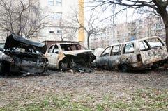 Os carros totalmente destruídos queimaram-se no fogo na zona de guerra ou em ascendente próximo das demonstrações civis fotografia de stock royalty free