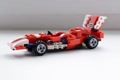 Os carros vermelhos do brinquedo, recolhidos do construtor estão na soleira na luz suave do dia imagem de stock royalty free