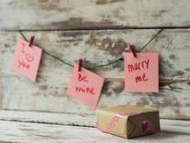 Os cartões do ` s da caixa de presente e do Valentim com os grampos vermelhos que penduram na madeira lançada à costa rústica tex Fotografia de Stock