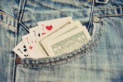 Os cartões e o dinheiro de jogo no brim azul pocket Fotografia de Stock Royalty Free