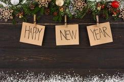 Os cartões, o ornamento e a festão da decoração do ano novo feliz moldam o fundo Fotos de Stock Royalty Free