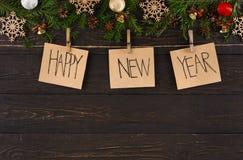 Os cartões, o ornamento e a festão da decoração do ano novo feliz moldam o fundo Imagem de Stock