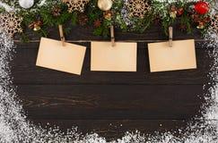 Os cartões, o ornamento e a festão da decoração do Natal moldam o fundo Imagens de Stock