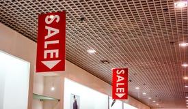 Os cartazes da venda na forma vestem o shopfront imagem de stock royalty free
