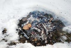 Os carvões ardendo sem chama do queimar-através do fogo na terra inflamado da neve imagens de stock royalty free