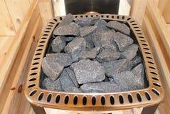 Os carvões pretos estão no fogão na sauna imagem de stock