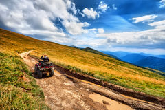 Os cavaleiros da bicicleta do quadrilátero do panorama ATV na montanha bonita ajardinam Foto de Stock