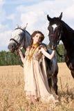 Os cavalos da preensão dois da mulher Fotos de Stock Royalty Free