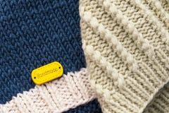 Os chapéus feitos malha de lã das crianças em um fundo claro Conceito da puericultura DIY imagens de stock