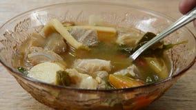 Os chaud et épicé de porc avec le tamarinier et la soupe thaïlandaise à herbes écopant par la cuillère banque de vidéos