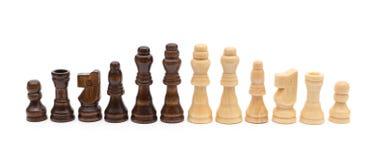 Os chesses pretos e marrons alinham no fundo branco Fotografia de Stock Royalty Free