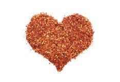 Os chillis esmagados quentes e picantes em um coração dão forma Foto de Stock Royalty Free