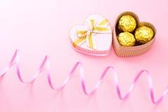 Os chocolates em um coração deram forma à caixa de presente com fita encaracolado imagens de stock royalty free