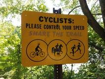 Os ciclistas amarelos satisfazem controlam sua parte da velocidade o sinal da fuga com símbolos fotografia de stock royalty free