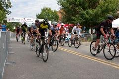 Os ciclistas correm abaixo da rua no começo de Georgia Criterium Foto de Stock