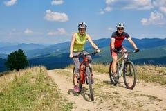 Os ciclistas de sorriso acoplam o homem e a mulher no sportswear e os capacetes que dão um ciclo bicicletas do corta-mato foto de stock royalty free