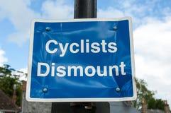Os ciclistas desmontam o sinal Imagens de Stock Royalty Free