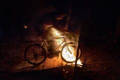 Os ciclistas saltam em uma bicicleta sobre um fogo na noite fotos de stock royalty free