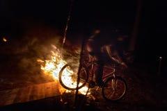 Os ciclistas saltam em uma bicicleta sobre um fogo na noite imagens de stock