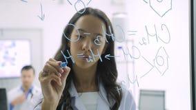 Os cientistas da investigação médica escrevem a fórmula científica em um whiteboard de vidro filme