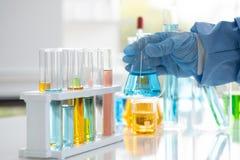 Os cientistas guardam um tubo de vidro ? disposi??o imagens de stock royalty free