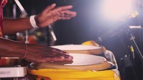 Os cilindros de bongos africanos do jogo do homem na noite do ar livre party entertainment Mãos que batem fastly o ritmo vídeos de arquivo