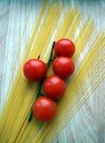 Os cinco tomates de cereja no ramo com espaguetes, fundo de madeira Fotografia de Stock Royalty Free