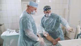 Os cirurgiões na sala de operações fazem o uzi dos pés pacientes do ` s Discuta o curso da cirurgia para remover as veias E vídeos de arquivo
