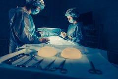 Os cirurgiões team o trabalho com monitoração do paciente na sala de operações cirúrgica Aumento do peito Fotos de Stock
