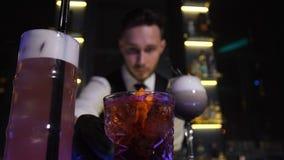 Os clientes de oferecimento do empregado de bar prepararam bebidas do cocktail vídeos de arquivo