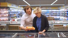 Os clientes masculinos e fêmeas empurram o carro com os produtos do mantimento no corredor do supermercado vídeos de arquivo