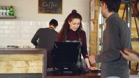 Os clientes novos estão pedindo o café para viagem no café e estão pagando-o com telefone esperto quando o caixa fêmea aceitar video estoque