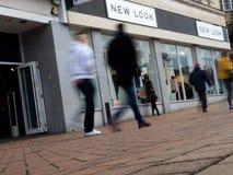 Os clientes que andam após New Look armazenam borrado no movimento Foto de Stock