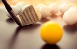 os clubes de golfe brancos e bolas de golfe uma amarelas no assoalho preto Mim Imagens de Stock
