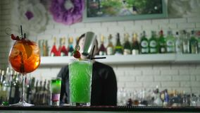 Os cocktail coloridos com bagas frescas estão no contador da barra e em fundo unfocused do barman executa truques com video estoque