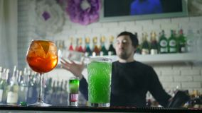 Os cocktail coloridos com close-up fresco das bagas estão na tabela da barra e em fundo unfocused do empregado de bar executa man vídeos de arquivo