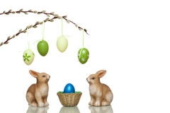 Os coelhos de Easter bonitos ao lado de Easter aninham-se com ovos Fotografia de Stock