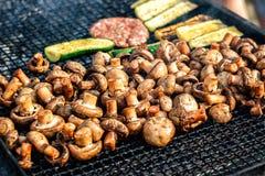 Os cogumelos brancos do cogumelo grelharam na grade ou o vapor do BBQ e gotas pequenas da água Cozinhando cogumelos na grade Foto de Stock