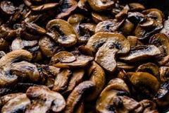 Os cogumelos cultivados cozinhados e cortados fecham-se acima da vista macro na bandeja foto de stock royalty free