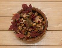 Os cogumelos e as bagas do viburnum em uma argila velha rolam em uma tabela de madeira Fotos de Stock