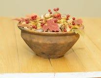 Os cogumelos e as bagas do viburnum em uma argila velha rolam em uma tabela de madeira Foto de Stock