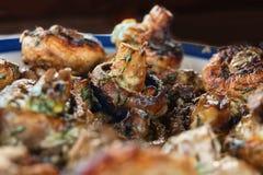 Os cogumelos inteiros roasted em uma grade com as especiarias da cor dourada Imagem de Stock Royalty Free