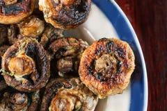 Os cogumelos inteiros roasted em uma grade com as especiarias da cor dourada Fotografia de Stock Royalty Free