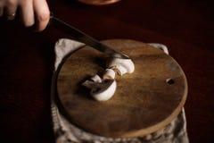 Os cogumelos são cortados em uma placa da cozinha Fotografia de Stock Royalty Free