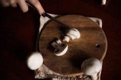 Os cogumelos são cortados em uma placa da cozinha Fotografia de Stock