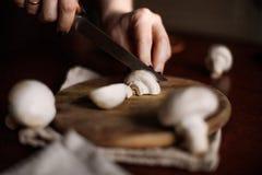 Os cogumelos são cortados em uma placa da cozinha Imagem de Stock Royalty Free