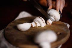 Os cogumelos são cortados em uma placa da cozinha foto de stock
