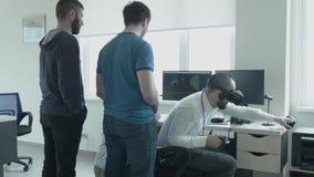 Os colaboradores de jogos da realidade virtual testam o jogo que criaram Os homens novos de Tvoe olham como o quarto homem com vi vídeos de arquivo