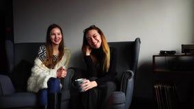 Os colegas bonitos da menina olham a câmera e riem do copo do chá durante a ruptura do trabalho e sentam-se em poltronas cinzenta video estoque