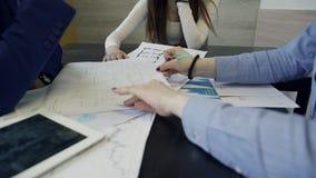 Os colegas de trabalho discutem os desenhos que sentam-se na tabela no escritório vídeos de arquivo